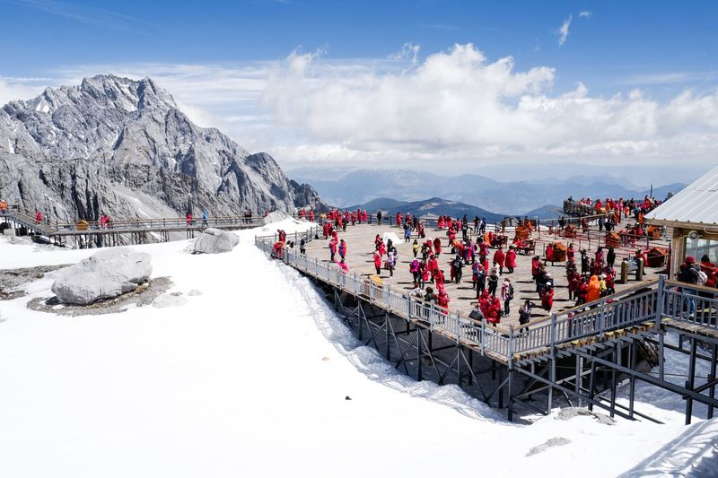 People over bridge on mountain against sky during winter