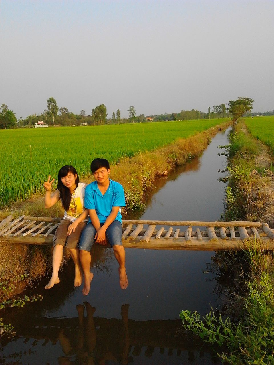 full length, two people, real people, togetherness, casual clothing, outdoors, plant, day, field, leisure activity, water, growth, nature, agriculture, grass, young men, sitting, clear sky, boys, lifestyles, bonding, landscape, young adult, young women, sky, men, tree, people