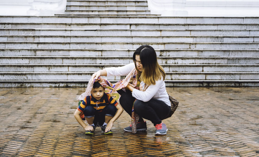 Mother and son crouching on footpath