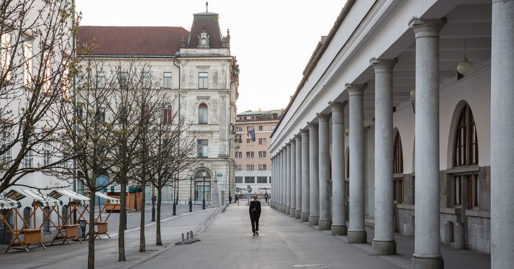 Rear view of person walking on street amidst buildings in city