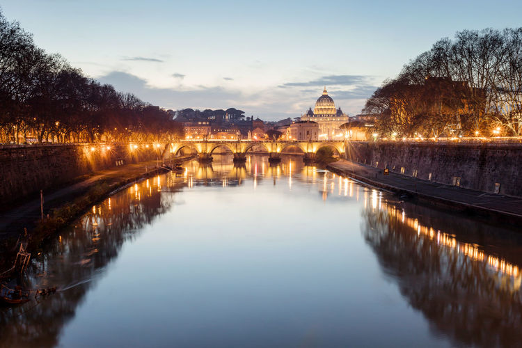 Tiber river and in the background the basilica of san pietro, in a panoramic view at the sunset.