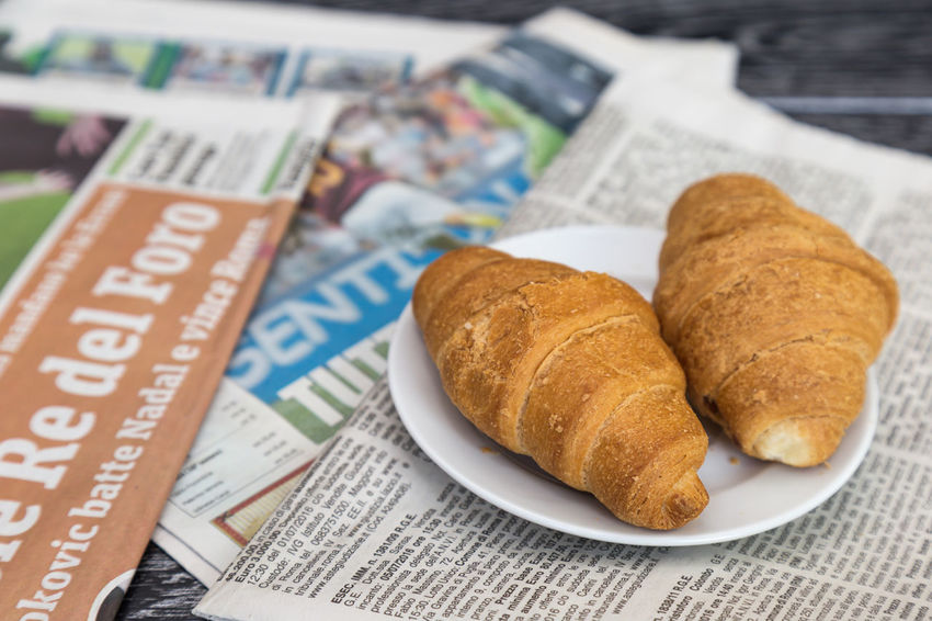 Italian newspapers on the table News Event Croissant Pastries Roll Desk Read Reading Ritual Article Developments Education Indoor Info Information Leisure Media News Newspaper No People Nobody Page Paper Publication Publish Reportage Story Table Printed Media Printing Out Magazine
