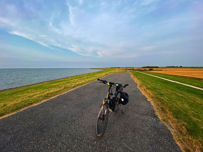 Bicycle on road amidst field against sky