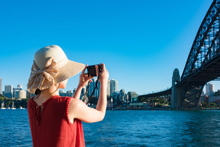 Rear view of woman photographing sydney harbor bridge against clear sky