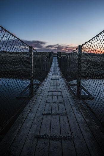 View of footbridge against sky during sunset