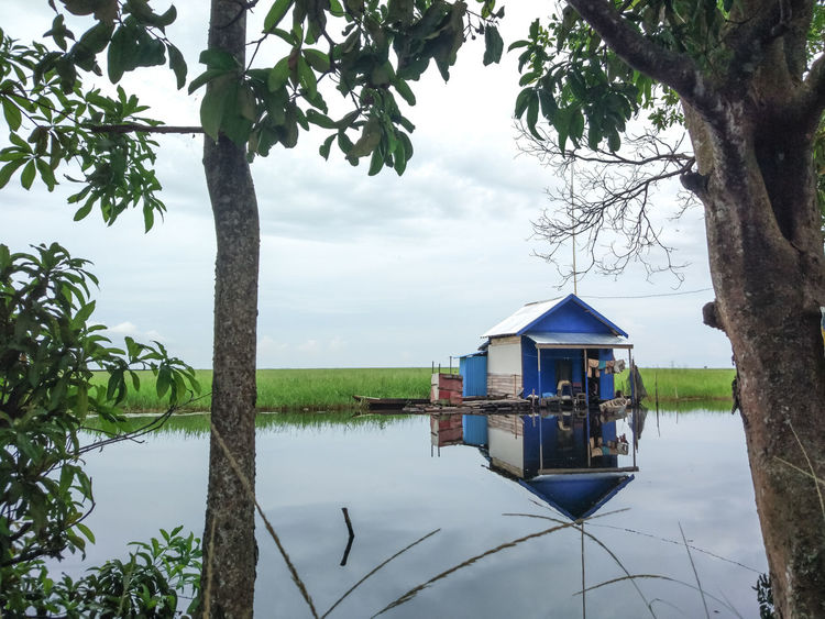 EyeEm Indonesia Landscape Landscape_Collection Tree Water Reflection Lake House Nature Outdoors Architecture Stilt House Tree Trunk Day Landscape Sky Beauty In Nature One Person Human Body Part Branch People Colour Your Horizn Adventures In The City Going Remote