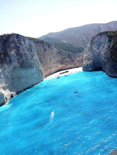 Navagio Beach Shipwreck Water Beauty In Nature Scenics - Nature Mountain Tranquil Scene Tranquility Sky Idyllic Blue Rock Waterfront Clear Sky Sea