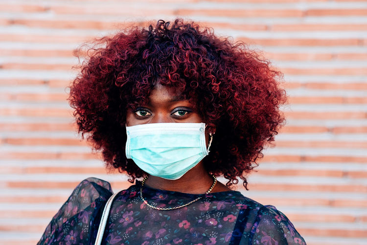 Close up portrait of young black woman wearing face medical mask to prevent coronavirus infection