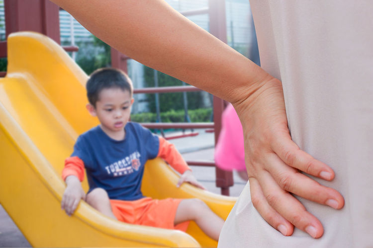 Cropped image of mother with hand on hip by son playing on slide