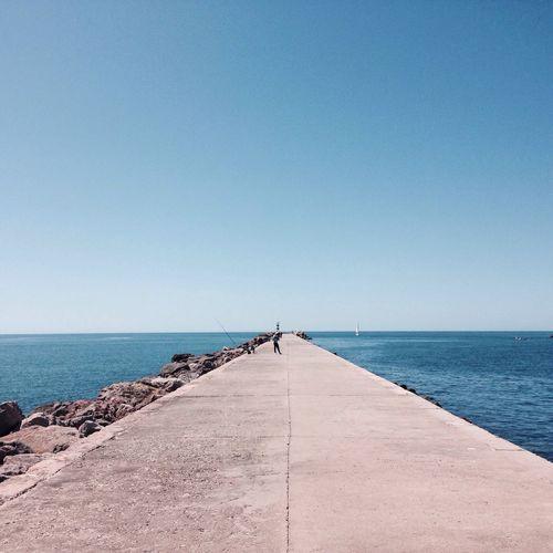 Pier On Sea Against Clear Blue Sky