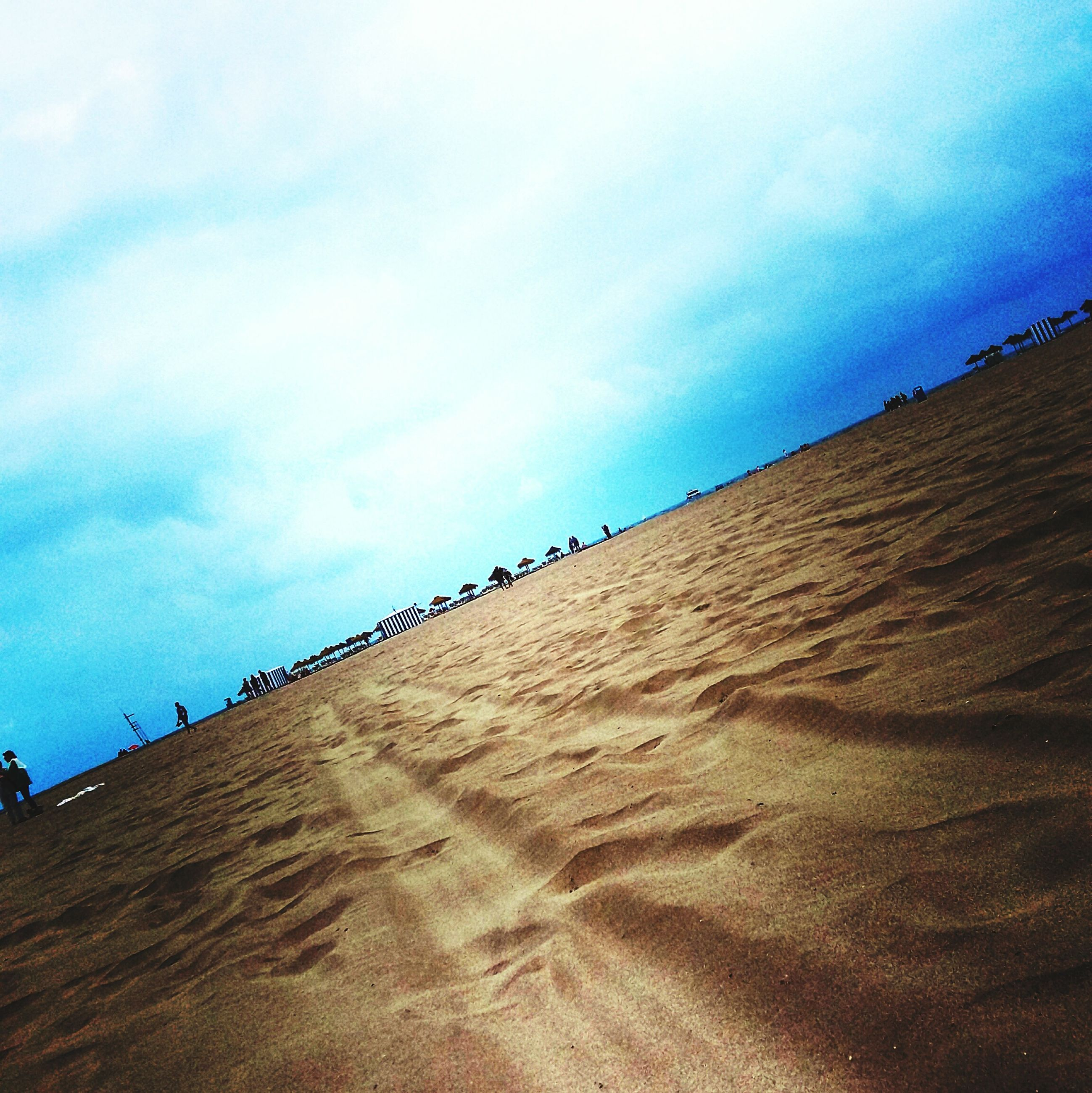sand, sky, beach, cloud - sky, tranquility, tranquil scene, blue, cloud, nature, scenics, cloudy, day, low angle view, built structure, beauty in nature, landscape, outdoors, desert, footprint, no people