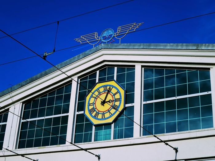 Architecture Blue Building Building Exterior Built Structure Circle City Clock Clock Face Day Geometric Shape Low Angle View Minute Hand Nature No People Outdoors Shape Sign Sky Time Window