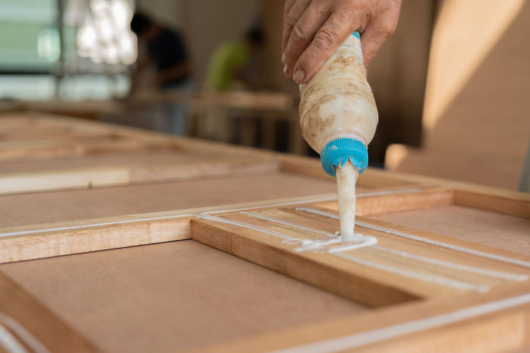 Close-up of hand pouring glue on wood