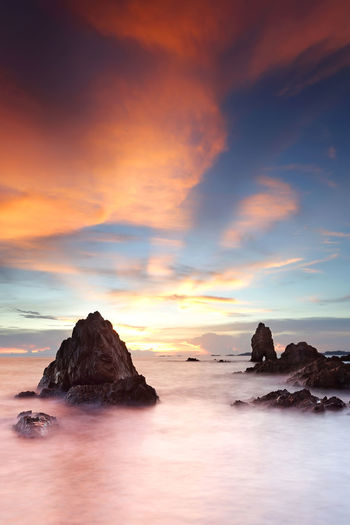 Beautiful sunset on tropical beach at Chonburi province, Thailand Sea Sky Water Rock Scenics - Nature Beauty In Nature Sunset Tranquil Scene Tranquility Solid Cloud - Sky Rock - Object Nature No People Idyllic Land Long Exposure Rock Formation Dramatic Sky Horizon Over Water Stack Rock