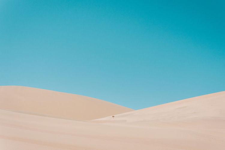 Sand dunes at desert against blue sky