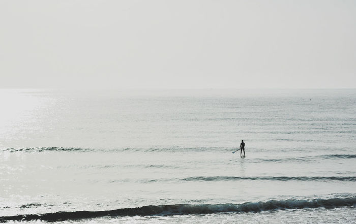 Day Aquatic Sport Vacations Outdoors Sport Nature Sky Wave Sand One Man Only Adventure One Person Silhouette Horizon Over Water Surfing Water Beach Sea Sunbeam Tranquility Clear Sky Minimal Llifestyle Paddle Boarding Paddle Surf