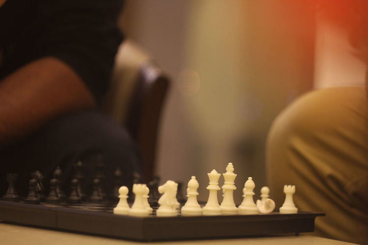 Close-up of people playing chess on table