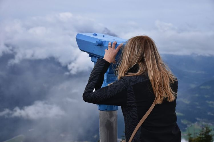 Rear view of woman looking through telescope