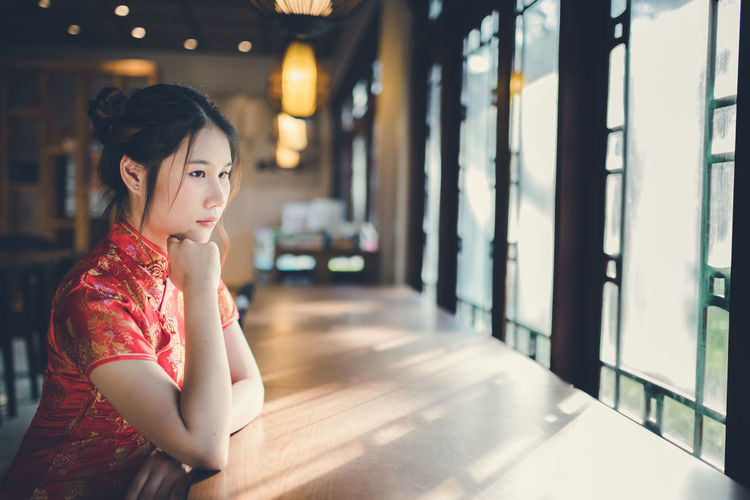 Thoughtful young woman looking through window while sitting in cafe