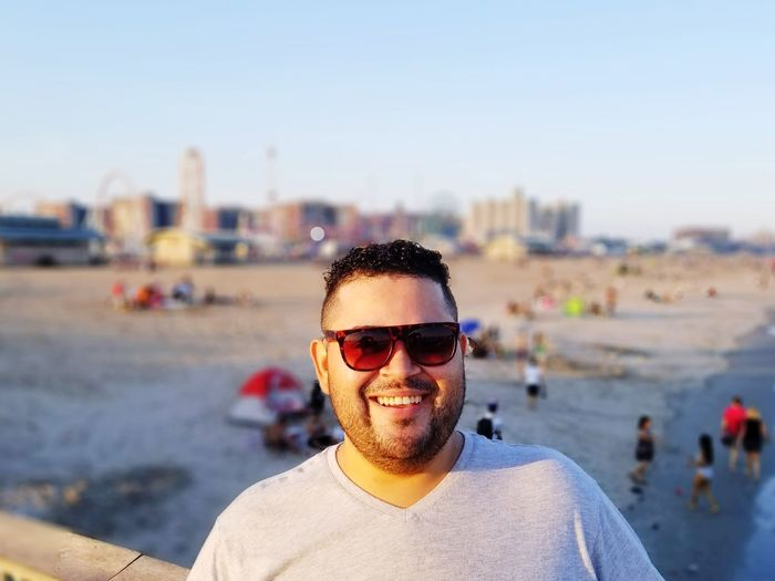Portrait of smiling man wearing sunglasses at beach against sky