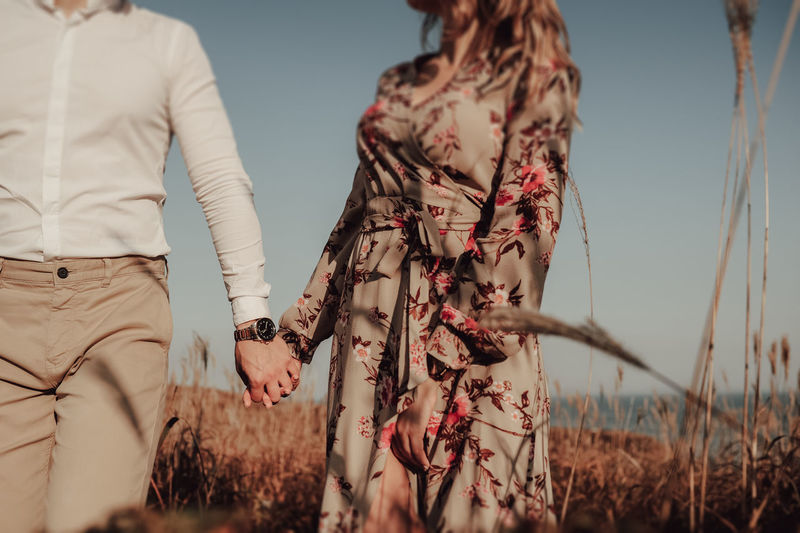 Woman in a print dress and  man in a white shirt holding hands in the middle of wheat field
