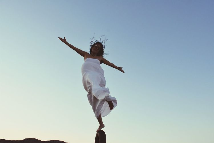 Low angle view of woman with arms outstretched against clear sky
