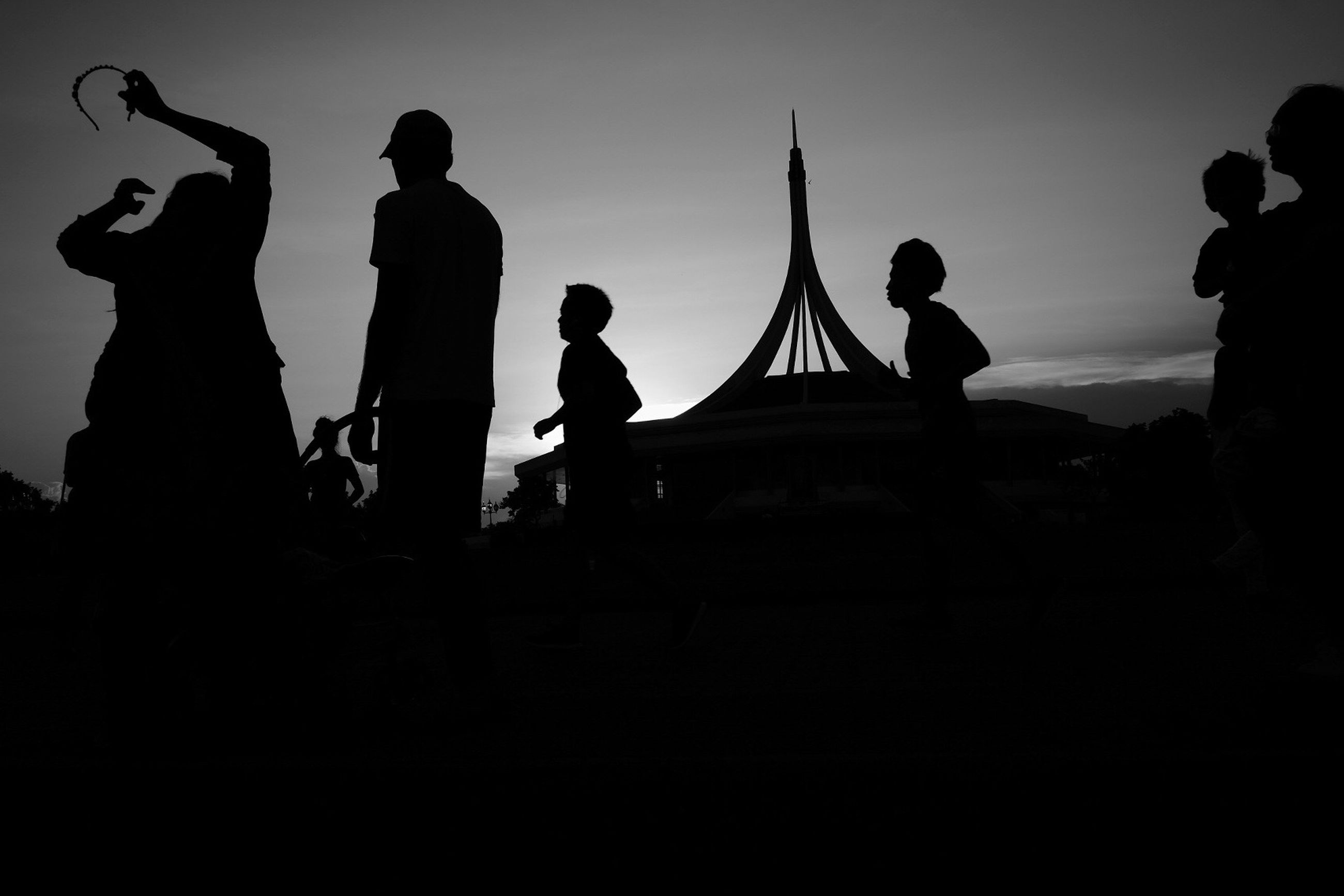 silhouette, arts culture and entertainment, men, togetherness, leisure activity, outdoors, real people, sky, amusement park ride, night, people