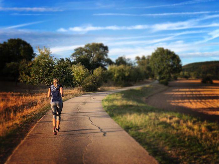 Full length of man running on road against sky
