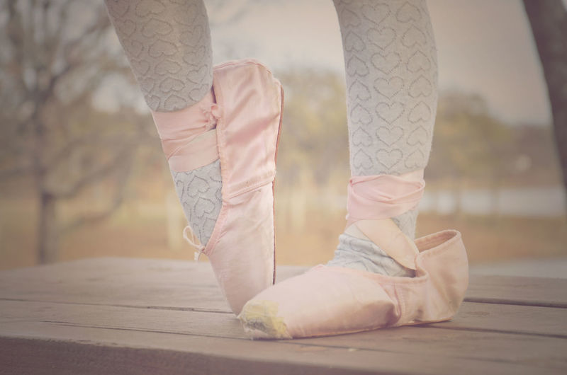 Low section of girl wearing ballet shoes