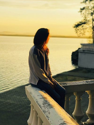 Woman looking at sea while sitting at railing against sky during sunset
