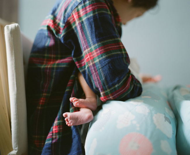 Midsection of woman breastfeeding baby at home