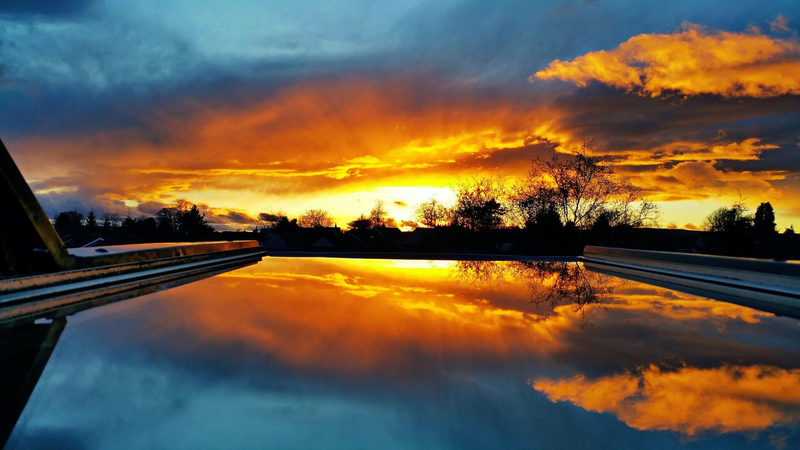 sunset, orange color, reflection, scenics, cloud - sky, tranquil scene, sky, cloud, water, transportation, tree, beauty in nature, tranquility, cloudy, nature, outdoors, dramatic sky, calm, majestic, moody sky, standing water, long, no people