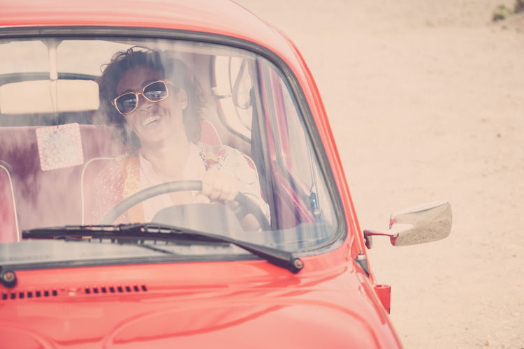 Cheerful happy lady caucasian middle age curly female smile and laugh driving her old retro beautiful car - woman insurance concept for happy people traveling One Woman Only Females Enjoying Life Freedom Red Car Vintage Casual Clothing Caucasian Car Mode Of Transportation Motor Vehicle Real People Glasses One Person Land Vehicle Women Portrait Leisure Activity Transportation Lifestyles Headshot Smiling Adult Happiness Front View Sunglasses Fashion Outdoors Hairstyle Young Woman 40-44 Years Fashion People