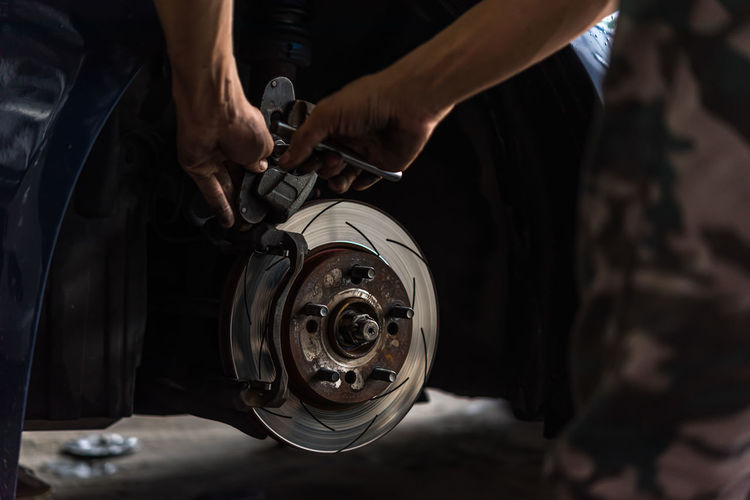 Cropped hands of mechanic repairing car wheel