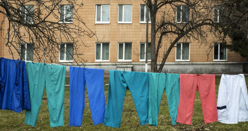 Color trousers are dried on the rope in the courtyard of the hospital Architecture Building Exterior Built Structure Chores Clothesline Color Courtyard  Day Domestic Life Dried Drying Hanging Hospital Laundry Multi Colored No People Outdoors Rope Sunlight Tree Trousers