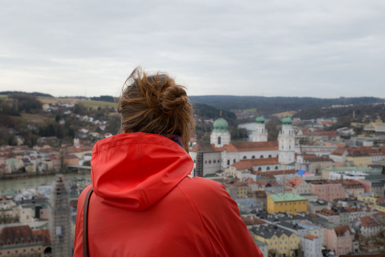 Rear view of woman looking at city buildings against sky