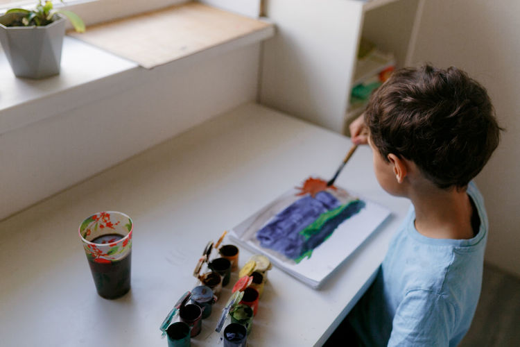 High angle view of boy painting at home