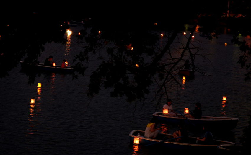 People on illuminated table against sky at night