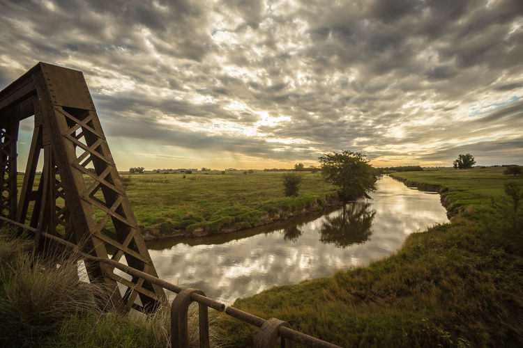 Scenic View Of River Throughfield Against Cloudy Sky