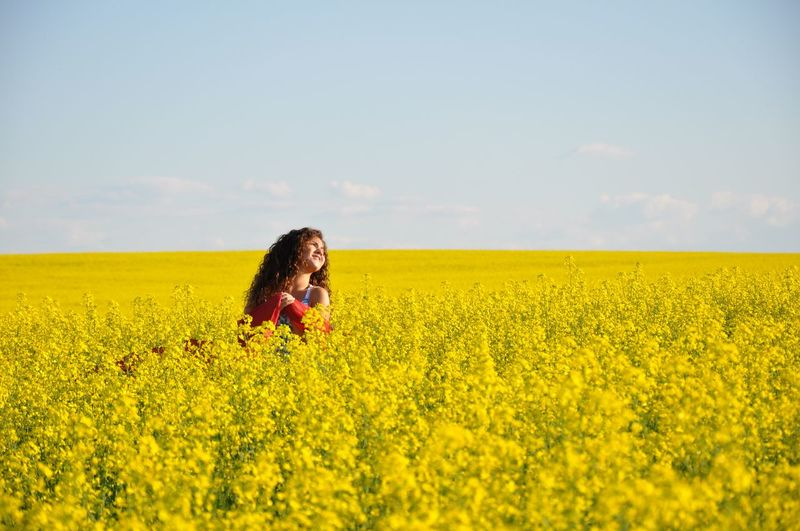 Teenage girl in oilseed rape field against sky