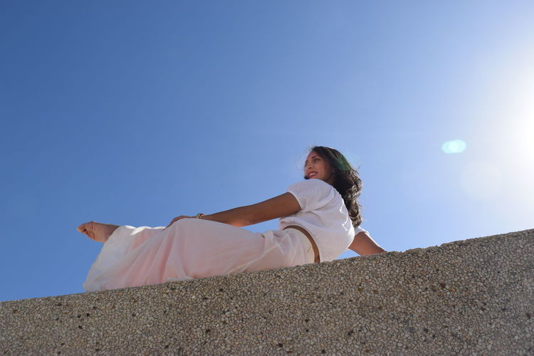 Low angle view of woman sitting on retaining wall against clear blue sky