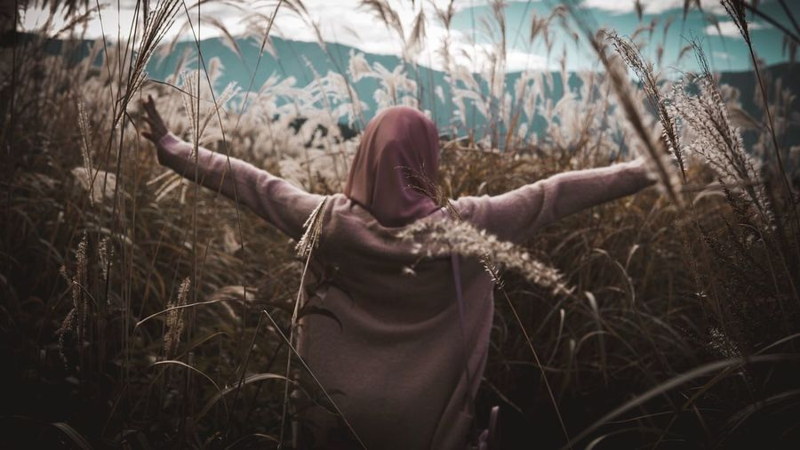 A girl wearing hijab standing inside ocean of lime grass with hand spread wide People Nature Real People Women Day Field Standing Outdoors Shades Of Winter Grass Plant Long Hair Growth Adult Young Adult One Person Rural Scene Young Women One Woman Only One Young Woman Only Only Women EyeEmTraveler An Eye For Travel Press For Progress Freedom