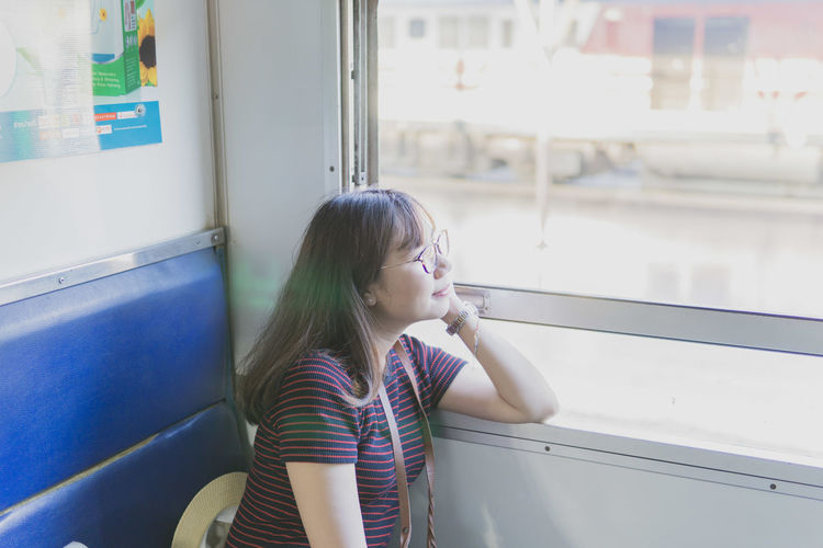 Side view of woman looking away through train window