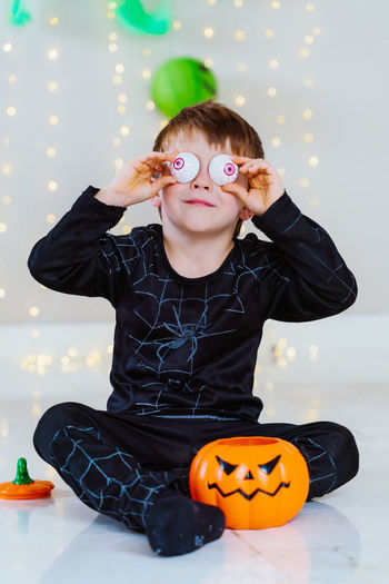 Portrait of cute boy holding pumpkin at home