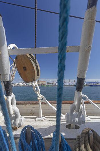Rope tied to bollard against blue sky