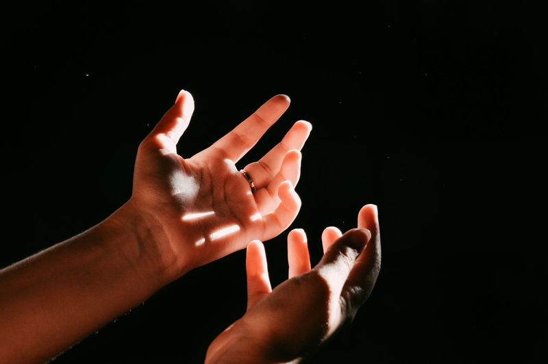 Cropped Hands Gesturing Against Black Background
