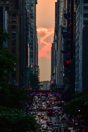 Traffic On City Street By Buildings Against Sky During Sunset