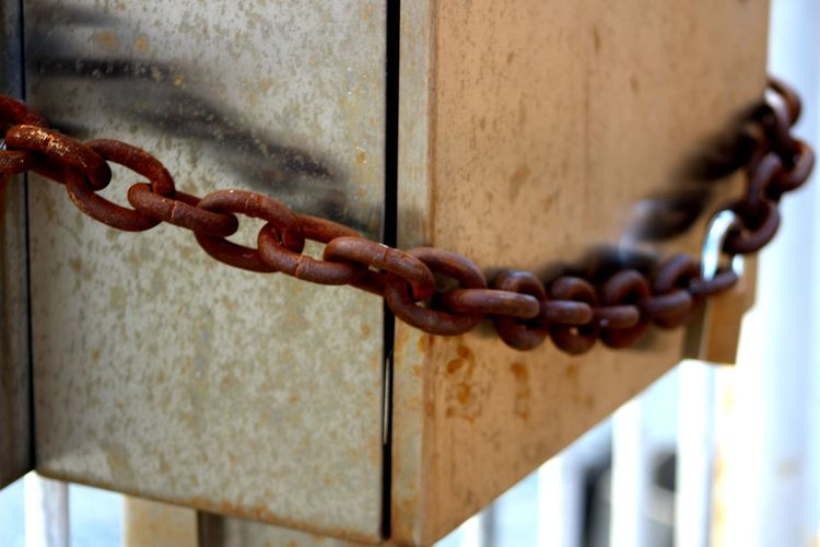Close-Up Of Metallic Box Locked With Rusty Chain