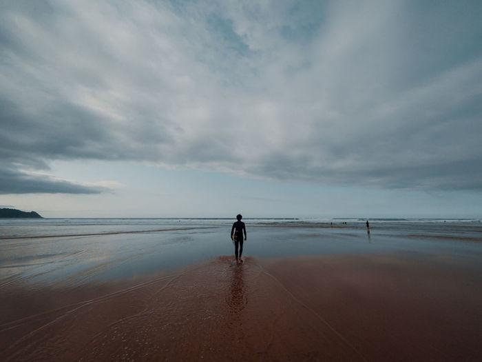 Rear view of silhouette man walking on beach