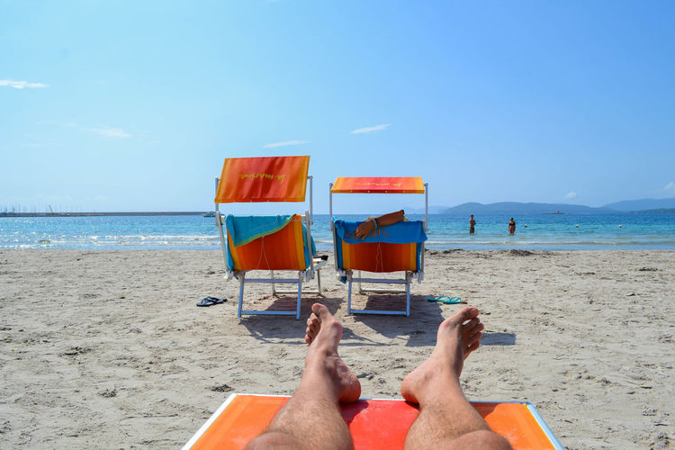 Low section of man resting on lounge chair at beach against blue sky